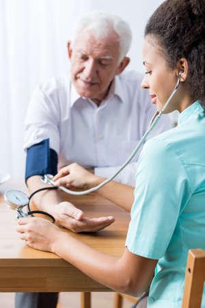 beside table: Carer taking seniors blood pressure, sitting beside table.