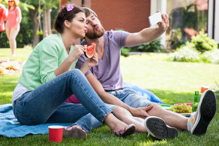 puckering: Man and woman puckering up and taking a self-portrait with mobile phone Stock Photo