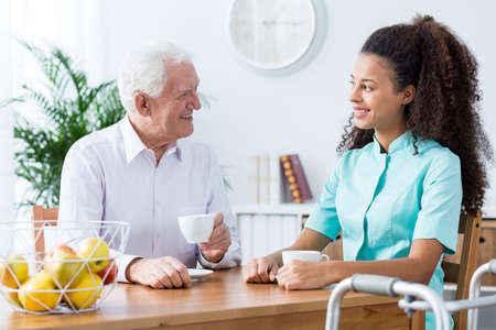 beside table: Carer and senior man drinking tea, sitting beside table in light room.