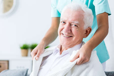 home care: Smiling elderly man having professional home care. Stock Photo