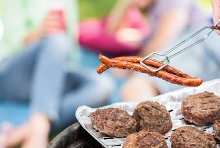 grill tongs sausage: Hamburgers and sausages on barbecue grill Stock Photo
