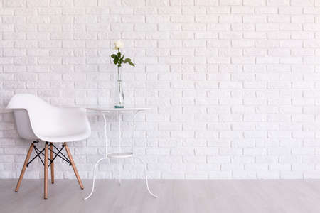 wall design: Shot of a white modern room with a chair and a table Stock Photo