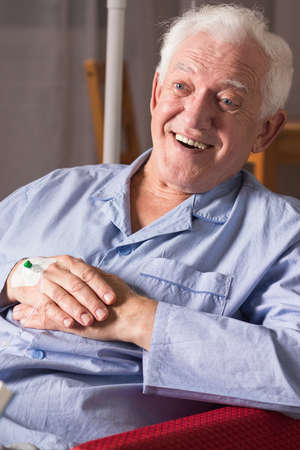 incurable: Positive senior man smiling, sitting on chair.