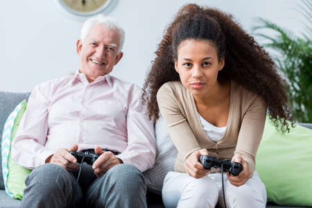 senility: Happy senior man and young afroamerican woman playing video games, sitting on sofa.