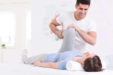 젊은 여자의 무릎에 공동 조작을 수행하는 젊은 물리 치료사의 총 스톡 콘텐츠