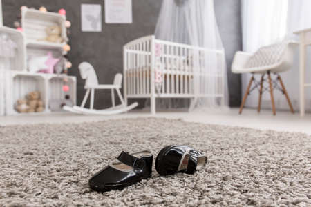 Shot of black baby shoes laying on a carpet in a nursery Stock Photo