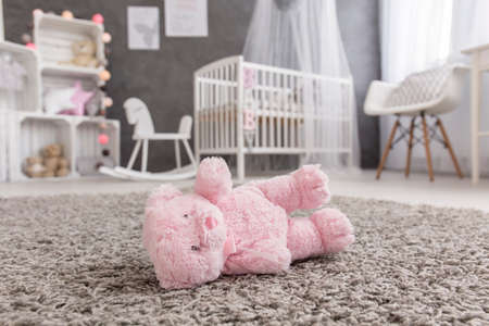 pink teddy bear: Shot of a pink teddy bear laying on a floor in a modern baby room