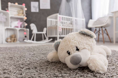 Shot of a teddy bear laying on a carpet in a cozy baby girl room