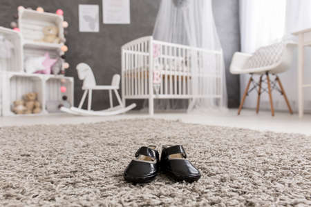 room decor: Shot of little baby shoes in a modern nursery