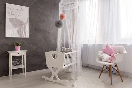 Shot of a cozy baby girl room with a big window Archivio Fotografico