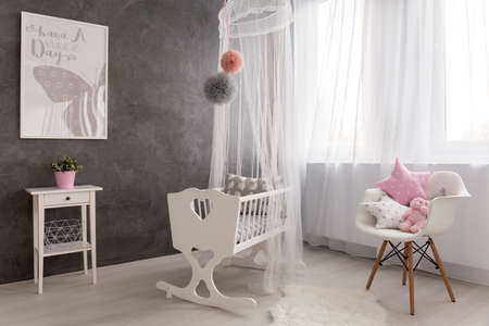 Shot of a cozy baby girl room with a big window Stock Photo