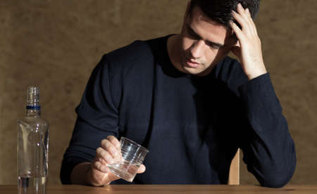beside table: Young man sitting beside table holding glass, bottle of vodca standing on a table