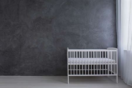 blank spaces: Shot of a little bed in an empty grey room Stock Photo