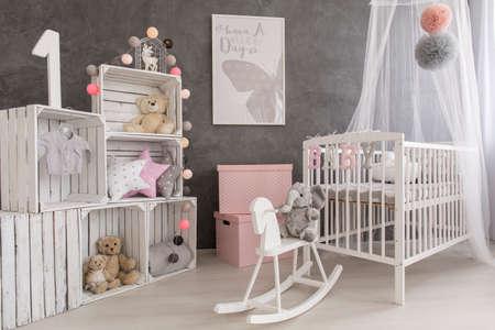 Disparo de un acogedor gris, sala de bebé blanco y rosa Foto de archivo