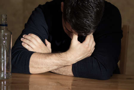beside table: Drunk man sitting beside table with his head down