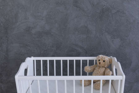 interior spaces: Shot of a teddy bear in a crib against a grey wall Stock Photo