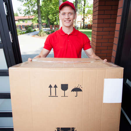Delivery man handing in a large cardboard box Фото со стока