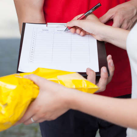 Close-up of a woman signing document of delivered package