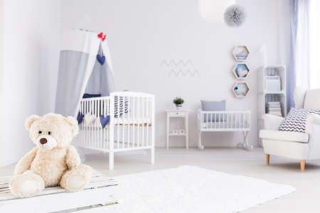 White baby room in marine style, teddy bear in the foreground