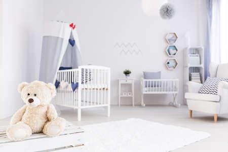 White babykamer in maritieme stijl, teddybeer op de voorgrond Stockfoto