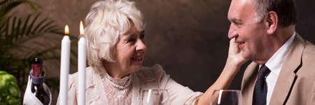 dinner date: Elderly couple during romantic candlelight dinner at restaurant