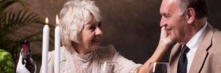 parejas enamoradas: Pareja de ancianos durante la cena romántica con velas en el restaurante
