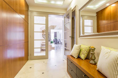 Functional hallway with wood details, mirror, and light floor tiles
