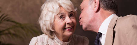 cheek to cheek: Elderly husband kissing his smiling wife on cheek