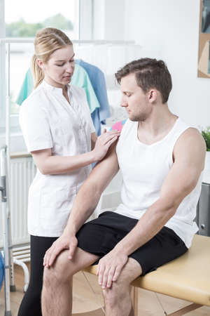 mobilization: Young beautiful physiotherapist at work in cabinet Stock Photo