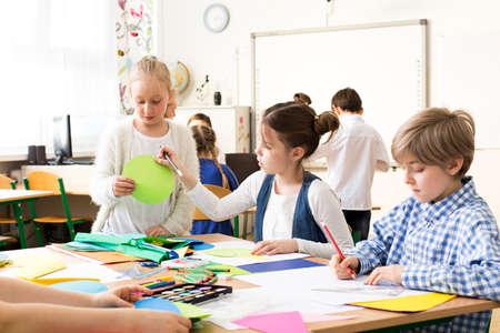 clases: alumnos felices que pintan las imágenes durante las clases de arte en la escuela. Sentado con amigos por una mesa