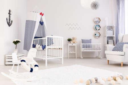 Ruime babykamer met eenvoudige witte meubels en mooie mariene decoraties Stockfoto