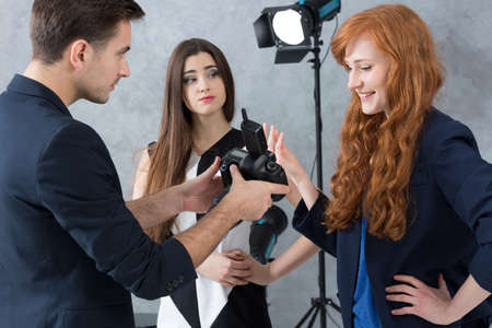 fussy: Young photographer talking to a designer with a criticising look on his face, next to a fussy model