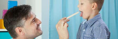 pediatra: Vista horizontal del pediatra examinando la garganta del ni�o Foto de archivo