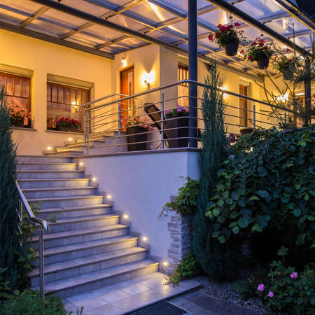 light house: Beautiful house with garden in the evening with lamps on Stock Photo