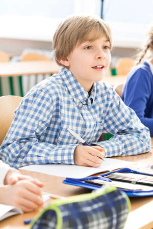 essay: Little cute excited boy writing an essay during school lesson. Sitting with friend in a school bend Stock Photo