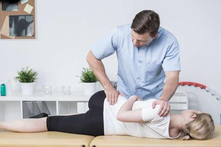 Mujer joven enferma en el consultorio del terapeuta físico Foto de archivo - 57970981