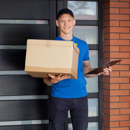 courier: Smiling courier holding cardboard box and clipboard