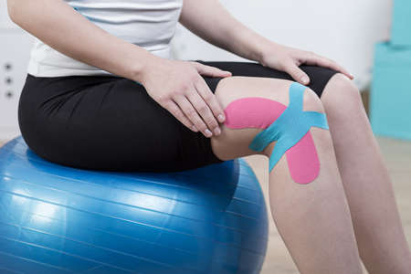 joint mobilization: Close-up of colorful kinesiology tapes on womans knee