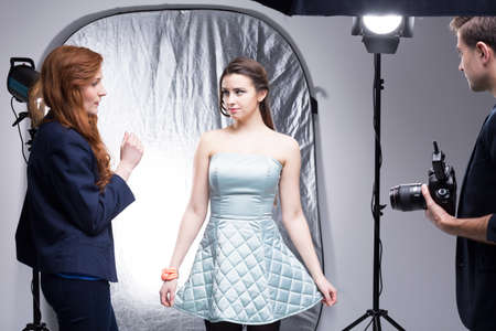 photo shoot: Photo studio with a female model, set manager and a photographer just before starting photo shoot