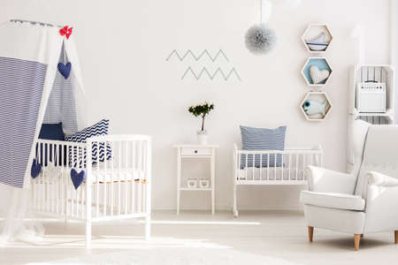 Infant Bedroom With Simple White Furniture And Decorations In Marine Style  Photo