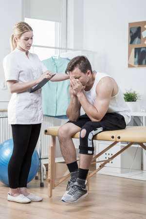 hurtful: Broken down young man with hurtful sick knee Stock Photo