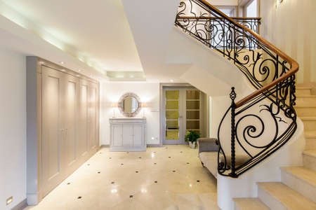 Light and spacious hallway with staircase with decorative railing 版權商用圖片 - 57928553