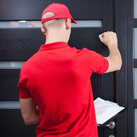 Achter mening van een levering man kloppen op de deur van de klant Stockfoto