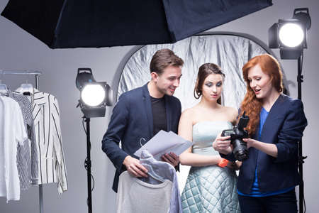 Young red-haired photographer in a photo studio showing photos on the camera display to a model and an assistant