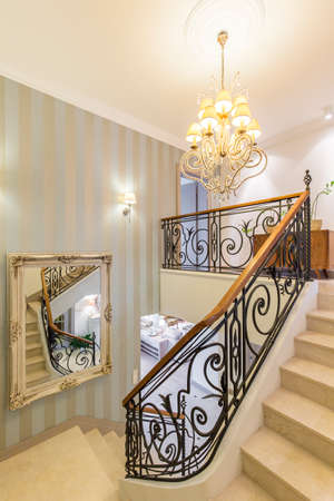 Beautiful staircase with crystal chandelier and decorative railing Stock Photo