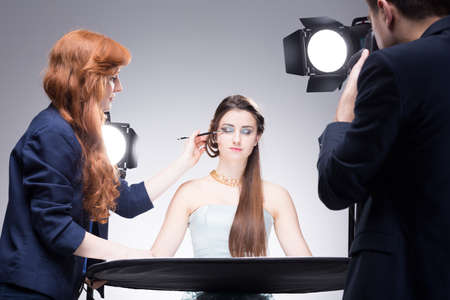 Young model having her strong makeup finished during shooting a portrait photo in a studio Foto de archivo