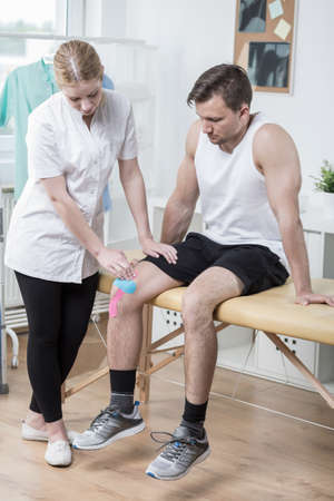 joint mobilization: Man with broken knee at young female physical therapist
