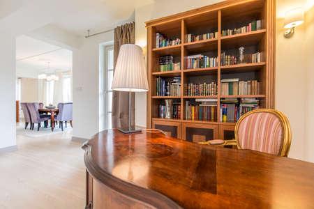 biblioteca: Amplia villa con oficina abierta en estilo colonial con gran escritorio de madera y una silla con estilo