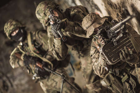 armed: Group of armed soldiers aiming from cover Stock Photo