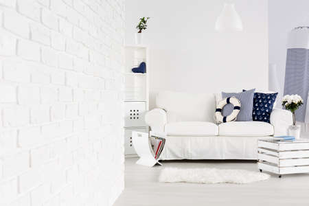 room decoration: White spacious living room with brick wall, sofa and decorations in marine style